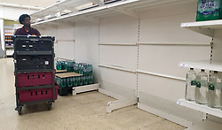 © Licensed to London News Pictures. 30/07/2021. London, UK. A Sainsbury's staff member walks past nearly-empty shelves of bottled drink water in Sainsbury's, north London. Record breaking numbers of people have been forced to self-isolate after being alerted by the NHS Covid-19 app. The pingdemic has seen staff shortages at supermarkets, resulting in less stock making its way to supermarket shelves. Labour leader Sir Keir Starmer has demanded that the government brings forward the end to self-isolation from 16 August to 7 August. Photo credit: Dinendra Haria/LNP