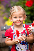 A young girl eats an ice pop as residents of I'on community celebrate Independence Day with a bicycle and golf cart parade July 3, 2013 in Mt Pleasant, SC.