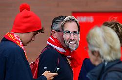 A Liverpool fan wearing a face mask of manager Jurgen Klopp