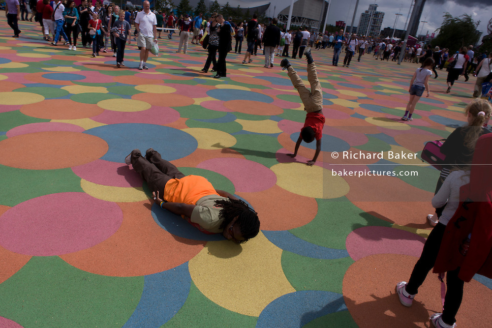 Spectators enjoy the grid-like patterned floor in the Olympic Park during the London 2012 Olympics. As a child does a cartwheel, a French lady lies on the ground to pose for a family photo. This land was transformed to become a 2.5 Sq Km sporting complex, once industrial businesses and now the venue of eight venues including the main arena, Aquatics Centre and Velodrome plus the athletes' Olympic Village. After the Olympics, the park is to be known as Queen Elizabeth Olympic Park.
