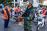 23 MAY 2014 - BANGKOK, THAILAND: A Thai soldier at a checkpoint in front of a group of motorcycle taxis in Bangkok Friday morning. The Thai military seized power in a coup Thursday evening. They suspended the constitution and ended civilian rule. This is the 2nd coup in Thailand since 2006 and at least the 12th since 1932. The army has ordered both anti-government protestors in Bangkok and pro-government protestors in the suburbs to go home and arrested leaders of both groups.    PHOTO BY JACK KURTZ
