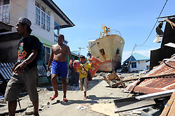 Oct. 5, 2018 - Donggala, Indonesia - People walk beneath the shadow of a ship washed into the street after the tsunami, while they search for salvageable items among the debris of a house in Donggala, Central Sulawesi. The death toll from Indonesia's multiple earthquakes and an ensuing tsunami jumped to 1,571, while search and rescue for the victims was extended. <br /> (Credit Image: © Agung Kuncahya B/Xinhua via ZUMA Wire)