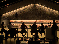 United States, Washington, Bellevue. Silhouettes of people on stools at a bar.