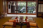 Indoor tea table by outdoor garden. Orikasan-dake / Orinasukan: hand woven fabric and kimono museum, , in Oiya-den, Kyoto, Japan. Kyoto Nishijin, hand-woven fabrics and period costumes and clothes from all over Japan.