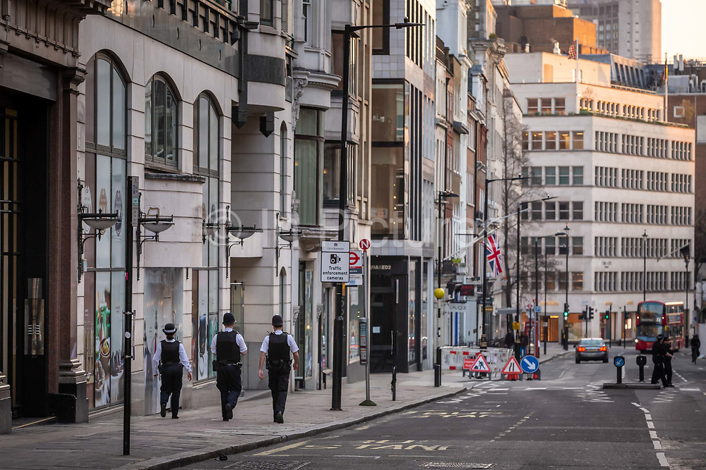 Three police officers patrol an almost deserted Conduit Street at what would normally be the evening rush hour in central London on March 27th, 2020. London is extremely quiet with almost every business closed and very few people about because of the Governments lockdown measures due to the Coronavirus crisis.