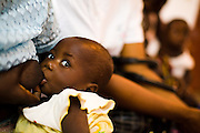 Kwaku Amoin Chimène breast feeds her eleven-month-old daughter Esther N'zi Amena while waiting at the NDA health center in Dimbokro, Cote d'Ivoire on Friday June 19, 2009.