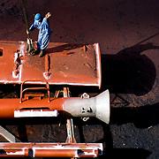 worker in blue jumpsuit gesturing on top of orange, metal structure