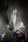 Nate Stevens explores narrow passages in an ice cave in Larsbreen, Svalbard.
