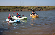 Canoeing in the tidal creek at Brancaster Staithe, north Norfolk coast, England
