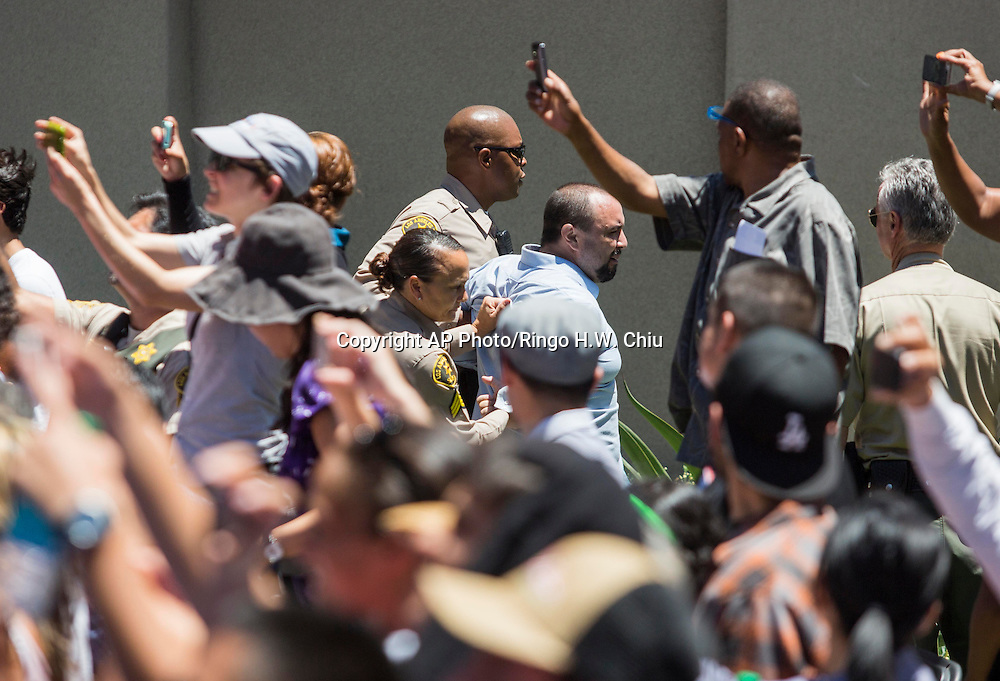 A protester is arrested by police officers while President Barack Obama speaks at Los Angeles Trade-Technical College in Los Angeles on Thursday, July 24, 2014.  (AP Photo/Ringo H.W. Chiu)