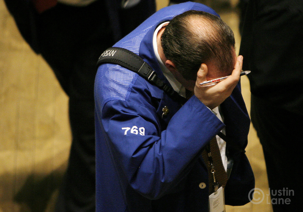 A trader rubs his forehead while on the floor of the New York Stock Exchange at the end of trading in New York, New York on Tuesday 27 February 2007. The Dow Jones Industrial average ended down 3 percent after China's equity market tumbled today.