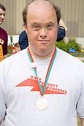 Athlete posing with summer games winning medal. Special Olympics U of M Bierman Athletic Complex. Minneapolis Minnesota USA
