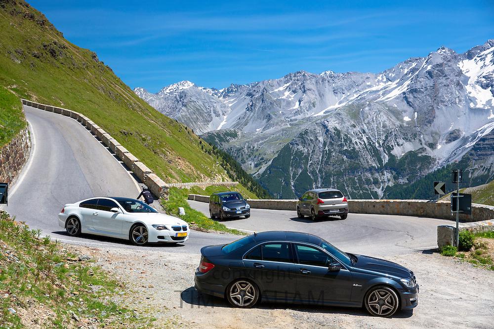 BMW M6 (white), Mercedes C63 AMG (black) Cars on The Stelvio Pass, Passo dello Stelvio, on route to Trafio in the Alps, Italy