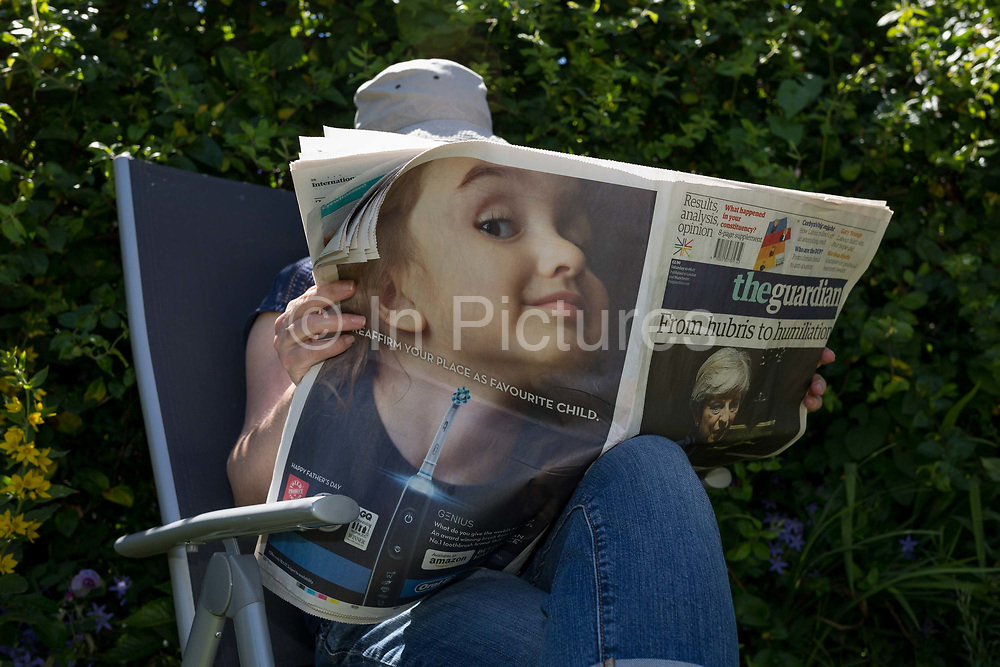 A middle-aged lady reads the Guardian newspaper featuring a toothbrush ad and Prime Minister Theresa May with the headline Hubris and Humiliation in a shady spot of her summer garden, Two days after the 2017 general election, on 10th June 2017, in London, England.