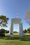 """The Peace Arch (1921) looking towards Canada.  Photographed from Peace Arch Historical State Park in in Blaine, Washington State, USA.  The Peace Arch was built in 1921 to commemorate the 100 year anniversary of treaties at the end of the War of 1812 between the USA and Great Britain. One side states """"Children Of A Common Mother"""", the other """"Brethren Dwelling Together In Unity""""."""