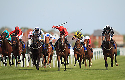 Ice Age ridden by Charles Bishop (red centre) wins the Starlight Brightening Lives Handicap Stakes at Newbury Racecourse.