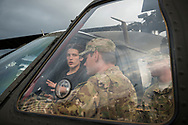 Riga, Latvia - August 01, 2015: The crew of a U.S. Army Blackhawk helicopter in the Latvian capital Riga talk with a civilian sitting in the pilot's seat. The helicopter had flown into the city to participate in the 100th anniversary celebration of the founding of the Latvian Riflemen battalions. The public was able to tour the inside of the vehicle.