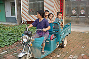 A woman carries her grand children in a motor rickshaw in a rural village near Fuyang, Anhui Province,  China on 28 August  2013.  As able-bodied adults seek work in cities in hopes of better income, more and more villages in China are inhabited mostly by the elderly and children.