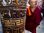 17 MARCH 2017 - KATHMANDU, NEPAL: A Buddhist monk spins a prayer wheel during morning prayers at Boudhanath Stupa in Kathmandu. The stupa is the holiest site in Nepali Buddhism. It is also the center of the Tibetan exile community in Kathmandu. The Stupa was badly damaged in the 2015 earthquake but was one of the first buildings renovated.     PHOTO BY JACK KURTZ