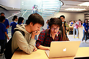 Customers look at various gadgets on offer during the opening of the Apple Inc's new store in Shanghai, China, on Friday, Sept. 23, 2011. Apple Inc. is currently has 5 stores in mainland China as it struggles to open enough stores to stave off competition of its popular iPhones and iPads