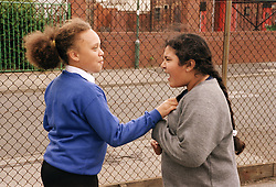 Two primary school girls arguing in playground,
