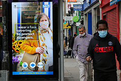 © Licensed to London News Pictures. 10/11/2020. London, UK. Shoppers with face coverings walk past the Government's campaign poster in north London as the national lockdown continues. The national lockdown in England until Wednesday 2 December, is in place to control the spread of COVID-19 cases. Photo credit: Dinendra Haria/LNP