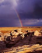 Rainbow above badlands, hoodoos and pedestal logs of Blue Mesa, Petrified Forest National Park, Arizona.