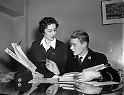 """12/11/1954<br /> 11/12/1954<br /> 12 November 1954 <br /> Aer Lingus workers Argina Galastegi and Bart Cronin prepare to stage """"Fly way Wild Eagle"""", pictured here discussing details at the Aer Lingus office on Cathal Brugha Street, Dublin."""