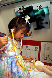 Stock photo of a young Asian girl playing doctor with her baby doll in a hospital room