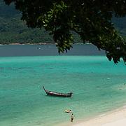Ko Lipe Sunrise beach (Bulow beach) with beach-goers and a boat, Thailand