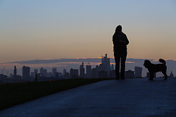 A roman walks her dog as day breaks over London's skyline, seen from Primrose Hill, to the north of the city. London, November 13 2018.