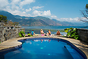 European tourists lounging by a pool in their hostel hotel in San Pedro la Laguna, on the banks of Lake Atitlan; Guatemala. Lake Atitlan is seen as the most important single tourist attraction in Guatemala; and is Central Americas deepest lake. There are many villages on the banks of the lake; each with different identity and culture; the majority of the population in the region identify as indigenous Maya and many still wear traditional dress and speak Maya languages.