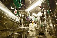 JPN, Japan: Okinawa Churaumi Aquarium, im Untergeschoss des Aquariums, aufwendige Technik zur Filterung des Wassers, Mechaniker inmitten glaenzender Rohrleitungen, Ocean Expa Park, Okinawa, Okinawa | JPN, Japan: Okinawa Churaumi Aquarium, inside the basement of the aquarium, complex technology for water filtring, mechanic between shiny tubes, Ocean Expo Park, Okinawa, Okinawa |