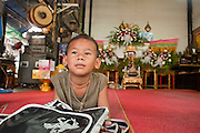 "Mar. 21, 2009 -- BANGKOK, THAILAND: A boy waits for a funeral to start in his home in the Monk's Bowl Village. The Monk's Bowl Village on Soi Ban Baat in Bangkok is the only surviving one of what were originally three artisan's communities established by Thai King Rama I for the purpose of handcrafting ""baat"" the ceremonial bowls used by monks as they collect their morning alms. Most monks now use cheaper factory made bowls and the old tradition is dying out. Only six or seven families on Soi Ban Baat still make the bowls by hand. Most of the bowls are now sold to tourists who find their way to hidden alleys in old Bangkok. The small family workshops are only a part of the ""Monk's Bowl Village."" It is also a thriving residential community of narrow alleyways and sidewalks.     Photo by Jack Kurtz"