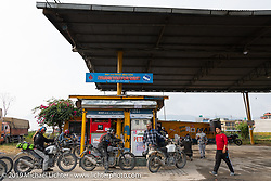 Motorcycle Sherpa's Bear Haughton getting his Royal Enfield Himalayan fueled at a gas stop on the Ride to the Heavens motorcycle adventure in the Himalayas of Nepal. Riding from Pokhara to the National Park in Chitwan, Monday, November 11, 2019. Photography ©2019 Michael Lichter.
