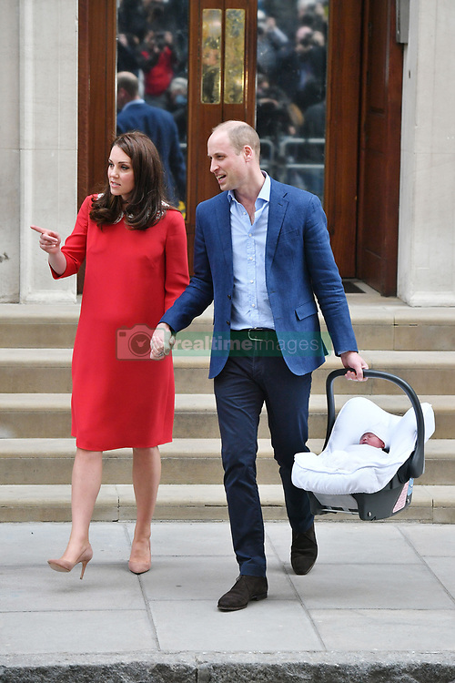 The Duke of Cambridge holds the hand of his wife, the Duchess of Cambridge, as he carries their newborn son from the Lindo Wing at St Mary's Hospital in Paddington, London.