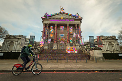 © Licensed to London News Pictures. 13/11/2020. LONDON, UK. A cyclist passes in front of the new Winter Commission at Tate Britain unveiled by British artist Chila Kumari Singh Burman.  Her installation on the façade references mythology, Bollywood, radical feminism, political activism and family memories in a celebration of neon light and swirling colour and is on display until 31 January 2021.  Photo credit: Stephen Chung/LNP