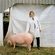 Alice with her pig. The hairdryers are out and the shampoo is flowing at the Great Yorkshire Show, one of Britain's biggest agricultural shows. Its famous for its competitive displays of livestock. The event, established in 1837, attracts over 125 000 visitors a year and has over 10 000 entries to its pedigree competitions ranging from pigeons and rabbits to bulls and shire horses. At the heart of the show is the passion of the exhibitors who spend hundreds of hours ( and pounds)  training, preparing and grooming their animals.