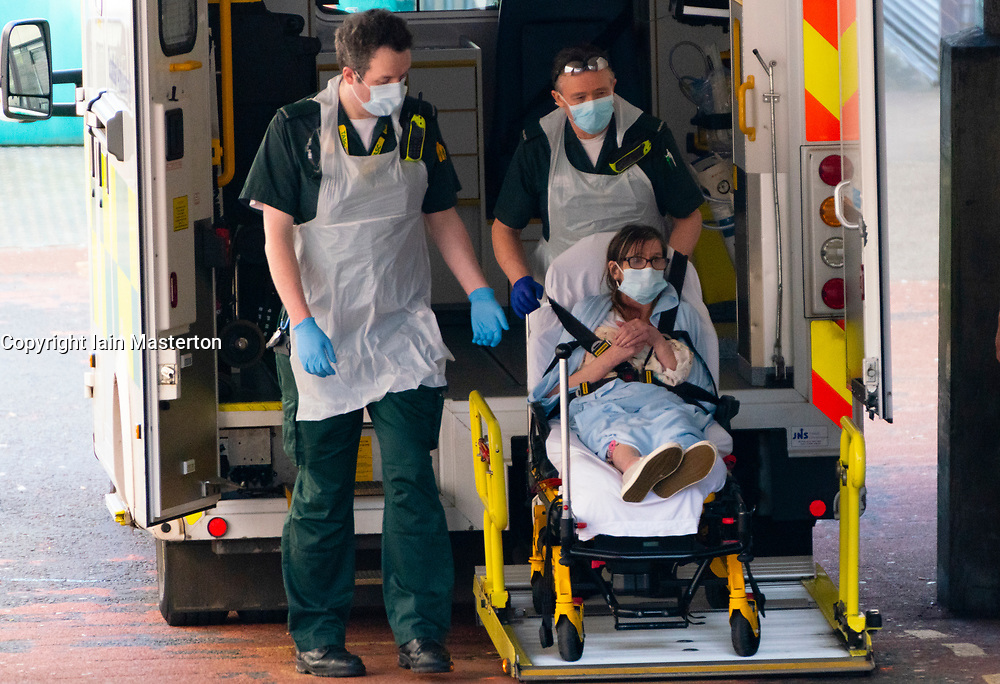 Glasgow, Scotland, UK. 15 April 2020. Patient is unloaded from ambulance by staff wearing PPE at A&E department at Glasgow Royal Infirmary. Iain Masterton/Alamy Live News