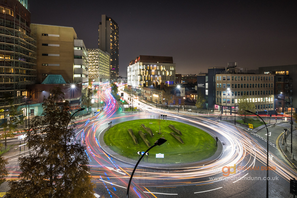 The colourful flow of traffic around Furnival Square roundabout in Sheffield. Photographed at dusk, the low light levels allowed for a long exposure and the capture of numerous light trails from the passing traffic. An urban landscape scene in South Yorkshire, England, UK.