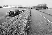 Nederland, Middelaar, 01-02-1995Eind januari, begin februari 1995 steeg het water van de Rijn, Maas en Waal tot record hoogte van 16,64 m. bij Lobith. Een evacuatie van 250.000 mensen was noodzakelijk vanwege het gevaar voor dijkdoorbraak en overstroming. op verschillende zwakke punten werd geprobeerd de dijken te versterken met zandzakken. Hier de situatie langs de Maas. Met extra zand probeert men het schuiven van de dijk te voorkomen.Late January, early February 1995 increased the water of the Rhine, Maas and Waal to a record high of 16.64 meters at Lobith. An evacuation of 250,000 people was needed because of flood risk. At several points people tried to reinforce the dikes with sandbags. Foto: Flip Franssen/Hollandse Hoogte