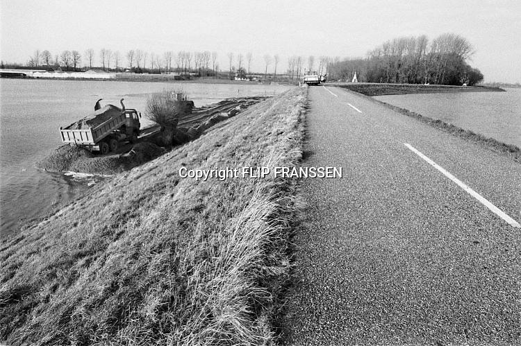 Nederland, Middelaar, 01-02-1995Eind januari, begin februari 1995 steeg het water van de Rijn, Maas en Waal tot record hoogte van 16,64 m. bij Lobith. Een evacuatie van 250.000 mensen was noodzakelijk vanwege het gevaar voor dijkdoorbraak en overstroming. op verschillende zwakke punten werd geprobeerd de dijken te versterken met zandzakken. Hier de situatie langs de Maas. Met extra zand probeert men het schuiven van de dijk te voorkomen.Late January, early February 1995 increased the water of the Rhine, Maas and Waal to a record high of 16.64 meters at Lobith. An evacuation of 250,000 people was needed because of flood risk. At several points people tried to reinforce the dikes with sandbags. Foto: Flip Franssen/Hollandse Hoogte