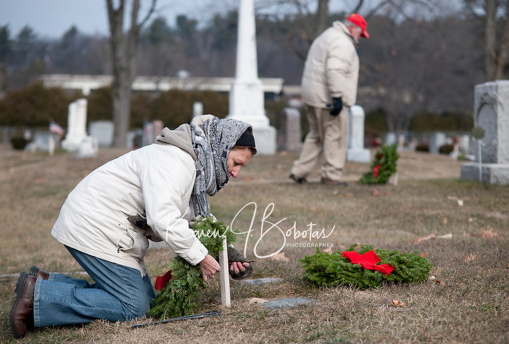 Chris St. Cyr offers a prayer after she places a holiday wreath on one of the 455 New Hampshire veterans graves at Bayside Cemetery on Saturday afternoon for Laconia Rotary's annual Wreaths across America event.  (Karen Bobotas/for the Laconia Daily Sun)