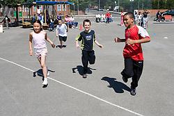 Children taking part in running race in school playground,