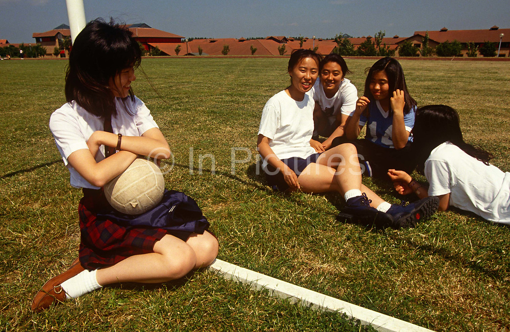Teenage girl students sit on the sports field during a lunchtime break at the Gyosei International Japanese School, a boarding school for Japanese ex-pats opened in 1987 in Willen Park, Milton Keynes, England. Giggling and smiling in their happy environment, the young women enjoy life in the UK, the children of skilled parents working in England. The Gyosei independent private school was the first of its type established in the country and shows the importance of Milton Keynes as a focus for Japanese investment.