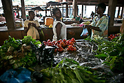 A farmer sell vegetables in an indoor market in Bangui.
