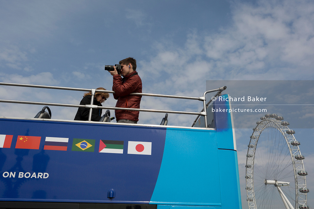 Tourists on a London tour bus, pass the London Eye, on 28th March, 2017, in London, England.