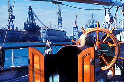 Cranes and drilling equipment seen from the deck of a sailboat in Galveston Texas