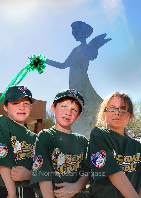 Freedom's Steadfast Angel of Love, a memorial to Christina Taylor-Green, was dedicated at Green Field, James D. Kriegh Park, Oro Valley, Arizona, USA.  Green, 9, who was the youngest victim killed during an assassination attempt of Arizona congresswoman Gabrielle Giffords, played little league baseball at the park.  The angel was created by artist, Lei Hennessy-Owen, with materials from Ground Zero in New York, the Pentagon, and the flight 93 crash sight, which were targeted by terrorists in the September 11 attacks.  Green was born on September 11, 2001. Players, Treyton Ellis, 6, (left), Trevor Ellis, 6, and Kayla Ravert, 7, show the patches on their uniforms that memorialize Green.