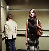 Woman looking over shoulder at man standing in corner of elevator.